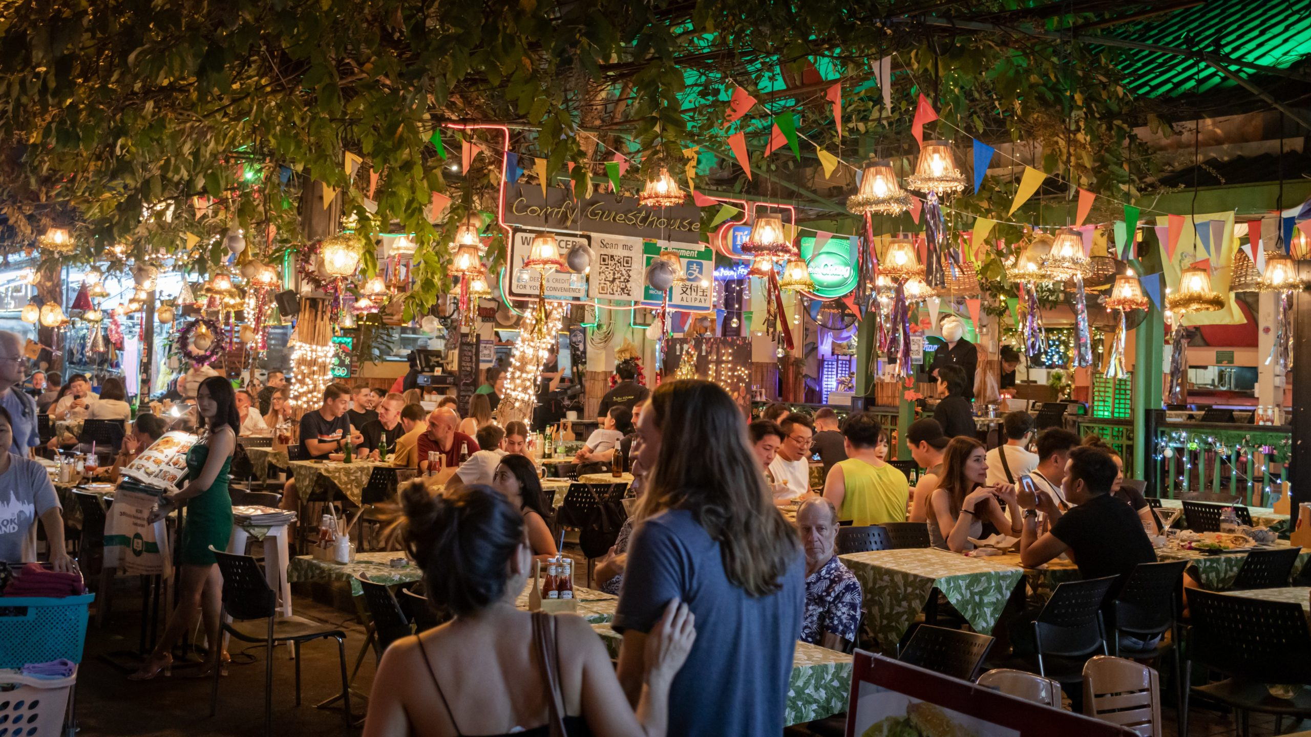 People in an open air restaurant at night time.